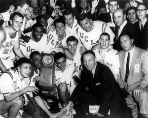 After winning his first title, John Wooden removed his glasses to celebrate with his 1964 championship team.